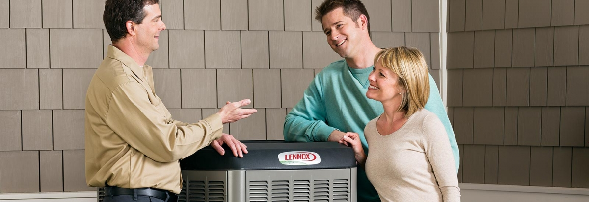 Service technician talking to a couple about their air conditioner